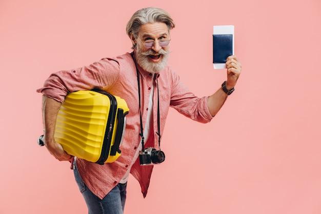 카메라와 함께 세련 된 턱수염이 난된 남자는 노란 가방 및 여권 티켓, 미소를 보유 하 고 여행 준비.