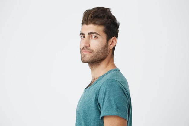 Elegante uomo barbuto con attraenti occhi scuri sul serio. ragazzo bello hipster con acconciatura alla moda e barba sul muro bianco