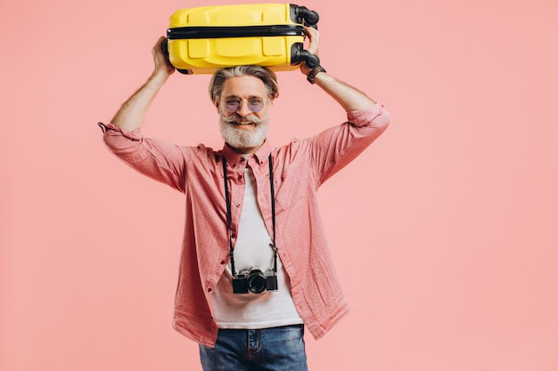 Stylish bearded man with a camera holds a yellow suitcase on head