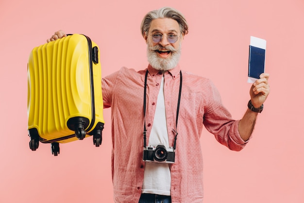 Stylish bearded man with a camera holds a yellow suitcase and a passport with a ticket, smiles and prepares for the trip.