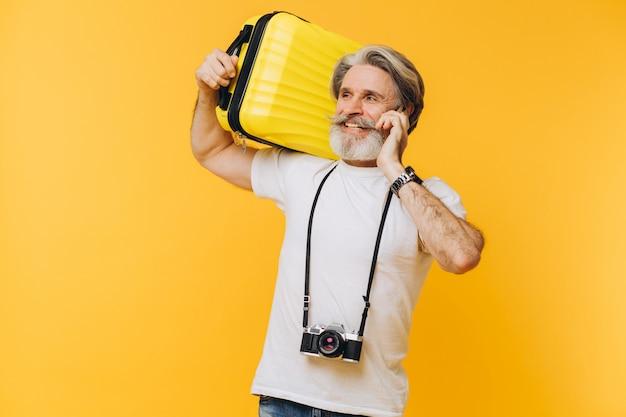 電話でチャット黄色のスーツケースを押しながら笑っているカメラでスタイリッシュなひげを生やした男
