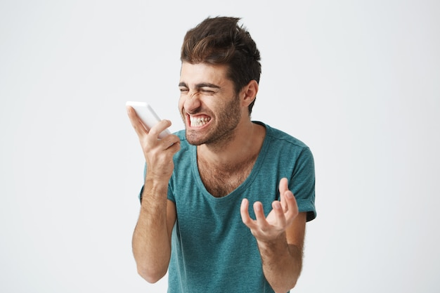 Stylish bearded man with dark hair angry shouting on the phone. angry and stressed man dressed in blue t-shirt screaming loudly in despair and anger, furious with noise coming from phone