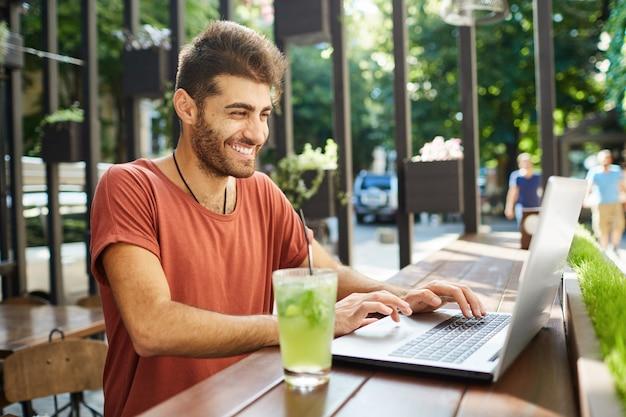Стильный бородатый мужчина с темными волосами, широко улыбающийся, в красной футболке, занят работой, пьет лимонад, освежая себя лимонадом. фрилансер, работающий на открытом воздухе, сидя за деревянным столом с не