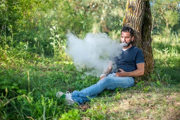 Стильный бородатый вейп-мужчина курит электронное дымовое устройство в лесу. вейп.