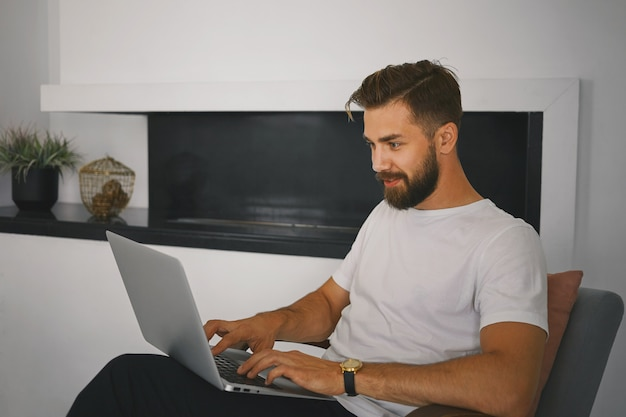 スタイリッシュなひげを生やした若い男性が自宅でポータブルコンピューターを膝の上に置いてリラックスし、出会い系サイトを介して興味深い女の子とオンラインでメッセージを送りながらキーボードを鳴らし、好奇心旺盛な楽しい表情をしています