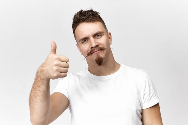 흰색 캐주얼 티셔츠에 스튜디오에서 포즈를 취하는 핸들 바 콧수염을 가진 세련된 수염 난 젊은 남성이 즐겁게 웃고, 제스처를 엄지 손가락으로 만들고, 좋은 영화를 승인합니다. 긍정 성과 승인 개념