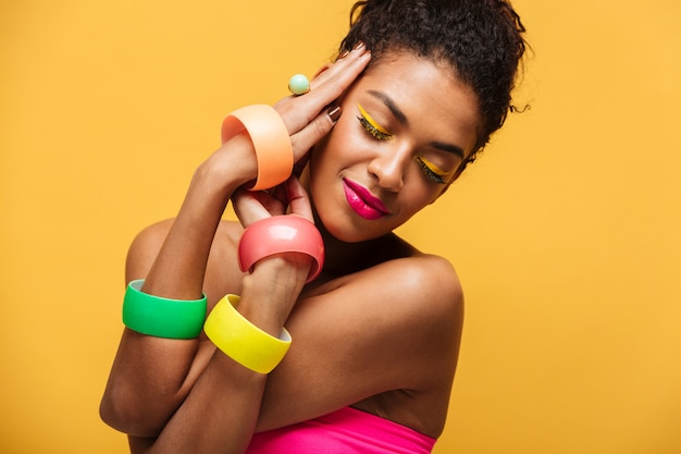 Stylish beautiful african american woman with bright makeup demonstrating multicolour jewelry holding hands at face isolated, over yellow