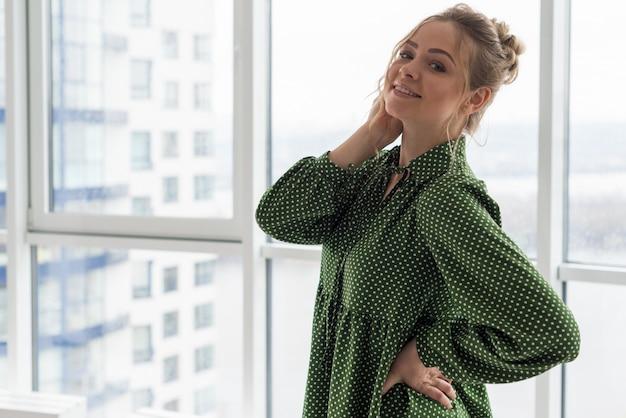 Стильная красивая белокурая девушка в небоскребе в офисе на фоне окна