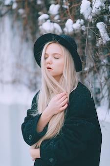 通りのフェンスの近くでポーズをとって黒い服と帽子のスタイリッシュな美しいブロンドの女の子
