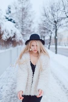 通りのフェンスの近くでポーズをとってコートと帽子のスタイリッシュな美しいブロンドの女の子