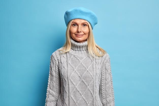 Elegante bella donna bionda indossa berretto francese e maglione lavorato a maglia sembra felicemente pronta per uscire durante la giornata autunnale.