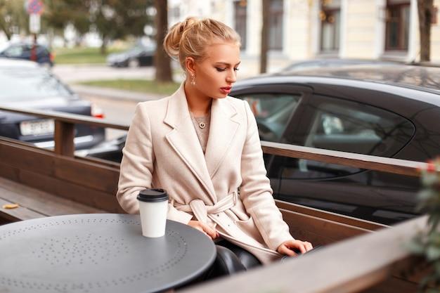거리에 카페에서 쉬고 고전적인 유행 코트에 세련된 아름다운 비즈니스 여성