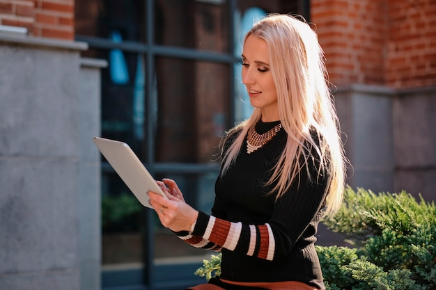 Stylish beautiful business woman with blond hair holding tablet pc, outdoors