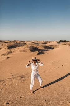 Stylish beautiful carefree happy woman walking in desert sand dressed in white trousers and blouse wearing straw hat on sunset