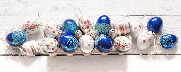 Стильная красивая композиция с синими пасхальными яйцами на белом деревянном.