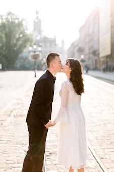Стильная красивая пара молодоженов азиатов прогуливается по улицам старого города, целуется, в солнечный день своей свадьбы