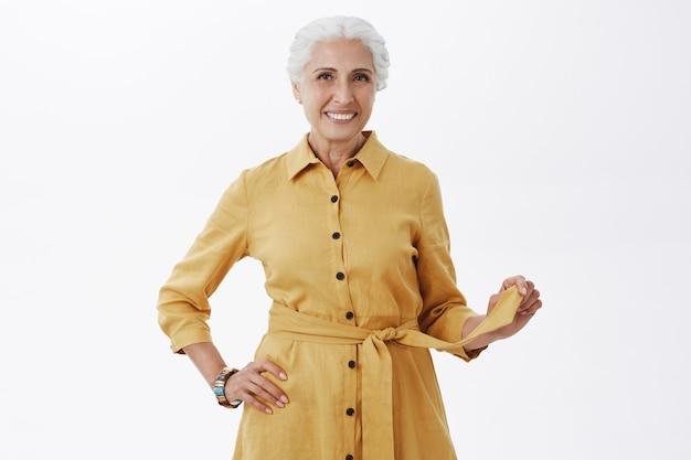 Стильная красивая пожилая женщина в желтом пальто улыбается