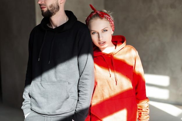 Стильная красивая модная пара в модной черно-красной толстовке с капюшоном в помещении с солнечным светом