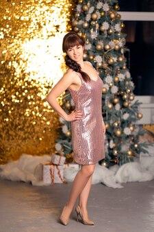 Стильная красивая девушка среди блесток и gerlands на рождественской вечеринке.
