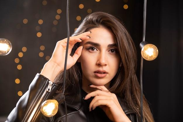 Elegante bella ragazza in vestiti di pelle nera su uno sfondo di lampade in studio.