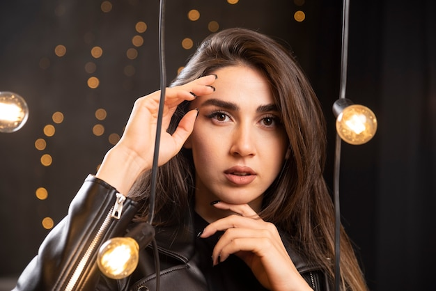 스튜디오에서 램프 배경에 검은 가죽 옷에 세련 된 아름 다운 소녀.
