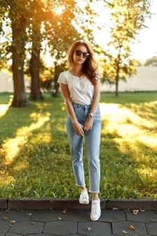 晴れた日に公園に立つおしゃれな服を着たスタイリッシュな美少女