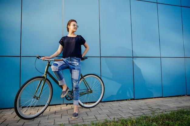 Stylish beautiful girl standing with vintage bike and looking away, near the blue wall, enjoying leisure time outdoors.