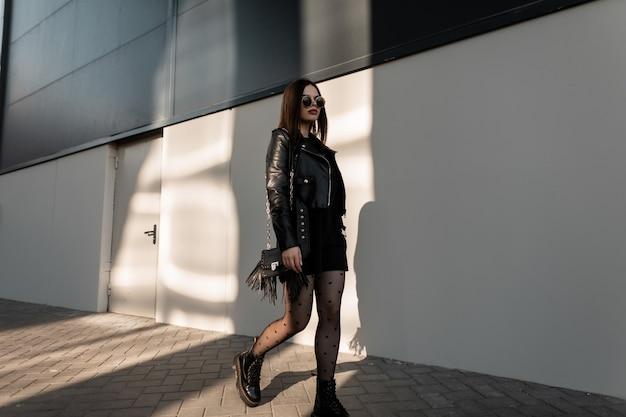 가죽 재킷, 검은 드레스, 섹시한 스타킹, 부츠, 검은 가죽 가방으로 세련된 록 옷을 입은 날씬한 몸매를 가진 세련된 아름다운 소녀가 도시를 걷는다