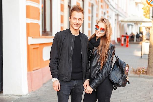 거리에 가방과 선글라스와 멋진 검은 옷에 세련된 아름다운 행복한 커플
