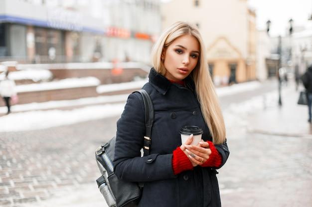 가방과 함께 패션 코트에 뜨거운 커피 한잔과 함께 세련된 아름다운 모델 소녀가 도시를 산책