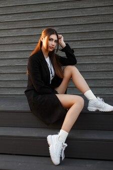 흰색 운동화와 검은 색 트렌디 한 코트에 세련된 아름다운 모델 여자는 목조 주택 근처 계단에 앉아