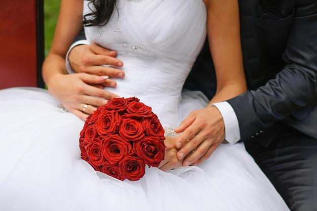 花嫁の手にバラのスタイリッシュな美しい赤いウェディングブーケ。新郎は花嫁を抱きしめる