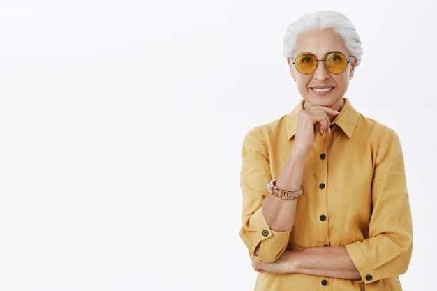 Стильная красивая старшая женщина в солнцезащитных очках улыбается