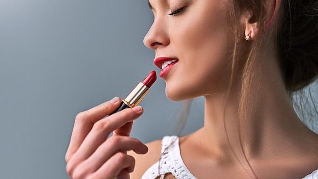 明るいマット赤い口紅を持つスタイリッシュな美しい官能的な白人女性モデル