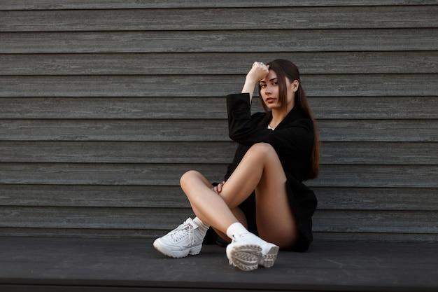 빈티지 집의 나무 벽 근처에 앉아 유행 옷에 세련 된 아름 다운 섹시 한 여자