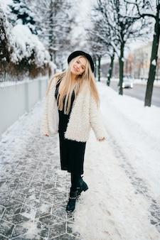 通りでポーズをとってコートと帽子のスタイリッシュな美しい笑顔のブロンドの女の子
