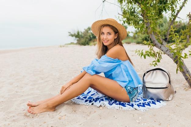 麦わら帽子、銀のバックパックを身に着けている熱帯のビーチで夏休みに細い足で砂の上に座っているスタイリッシュな美しい笑顔の女性