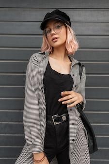 メガネ、革のバッグ、キャップ付きのファッショナブルなカジュアルな服を着たピンクの髪のスタイリッシュな美しい10代の少女が金属の門の近くに立っています