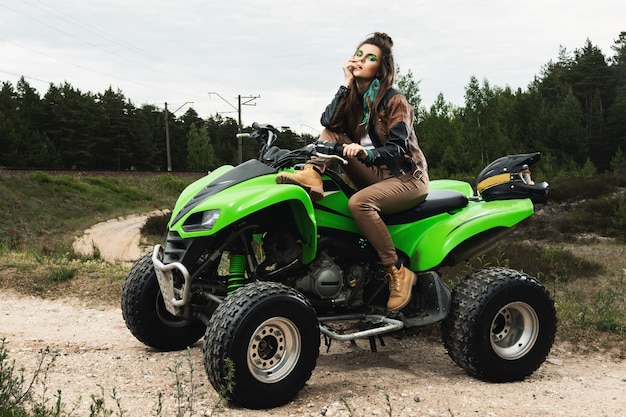 Stylish and beautiful woman and the atv on the forest road