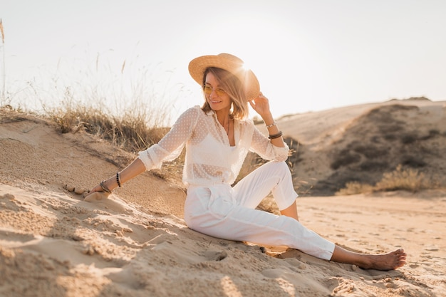 Stylish beautiful woman in desert beach sand in white outfit wearing straw hat on sunset