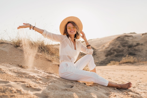 Stylish beautiful woman in desert sand in white outfit wearing straw hat on sunset