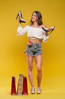 黄色の壁に買い物袋や靴を保持しているスタイリッシュな美しい女性