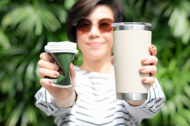 A stylish beautiful woman holding takeaway coffee cup in both hands, one is a single use paper cup with plastic lid the other one is a reusable stainless tumbler. no straw and zero waste concept.