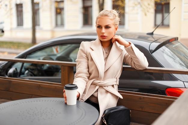 야외 테이블에 앉아 커피 한잔과 함께 고전적인 유행 코트에서 세련된 아름다운 여자