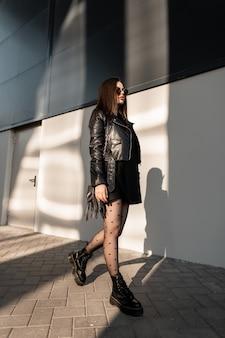 サンゴーグルを身に着けているスタイリッシュなバッグとファッショナブルな黒い服を着たスタイリッシュな美しい女性は、太陽の光で街の建物の近くを歩きます