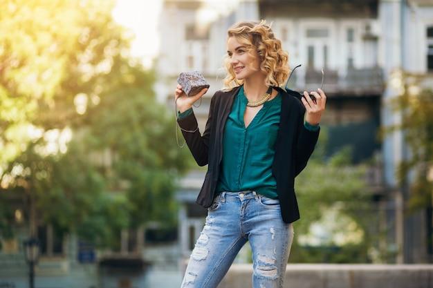 작은 지갑, 우아한 스타일, 봄 패션 트렌드로 거리를 걷는 청바지와 재킷의 세련된 아름다운 여인