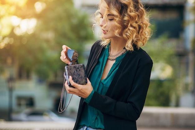 小さな財布、エレガントなスタイル、春のファッショントレンドで通りを歩くジーンズとジャケットのスタイリッシュな美しい女性