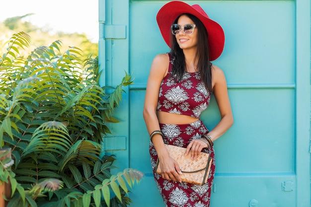 青い壁にポーズをとる赤い帽子のスタイリッシュな美しい女性、印刷された衣装、夏のスタイル、ファッショントレンド、トップ、スカート、スキニー、わらのハンドバッグ、サングラス、アクセサリー、笑顔、幸せ、熱帯の休暇