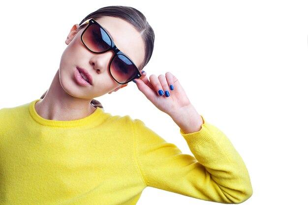 サングラスと明るいセーターでスタイリッシュな美しい女性