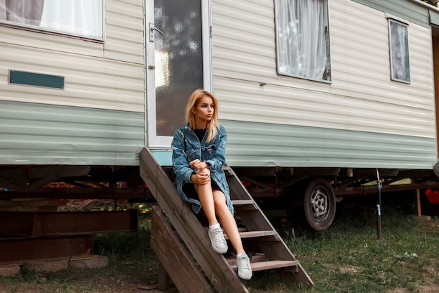 트렌디 한 데님 옷을 입은 세련된 아름다운 여인이 밴 근처의 나무 계단에 앉아 있습니다.